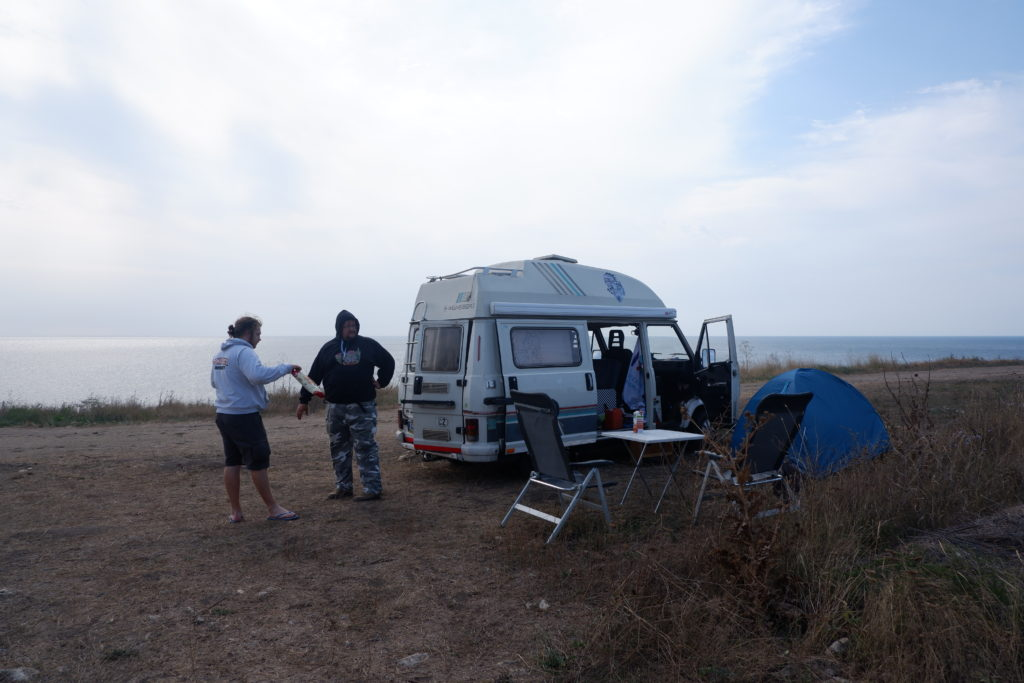 Caravan parked on a cliffy shore.